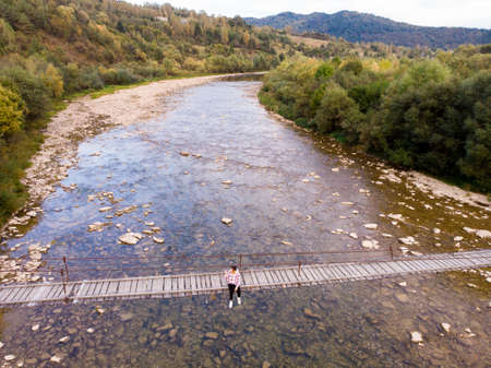 Aerial top drone view of woman traveler on wooden bridge over mountains river, autumn travel concept. 스톡 콘텐츠