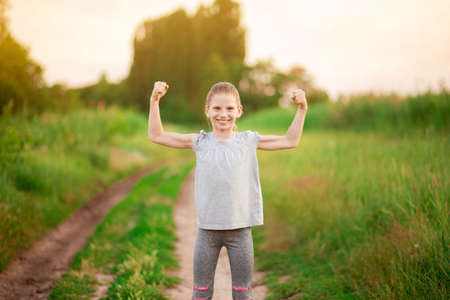 Child cute girl show biceps gesture of power and strength outdoor. Feel so powerful. Girls rules concept. Strong and powerful.