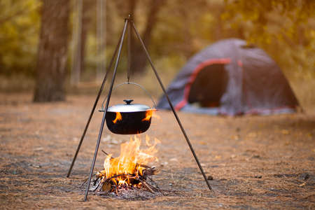 Hiking pot in bonfire with blue tent in autumn forest traveling