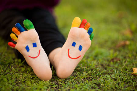 Close up of child human pair of feet painted with smiles outdoor in sunny park