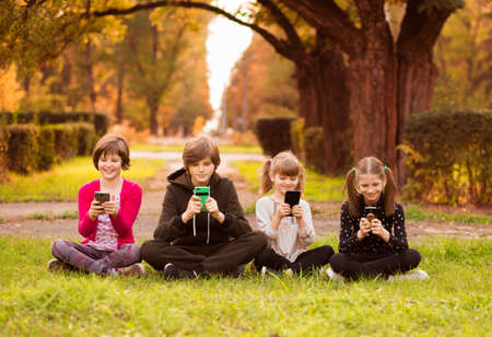 Children girls using mobile phones and chatting on social networks In park in everyday life