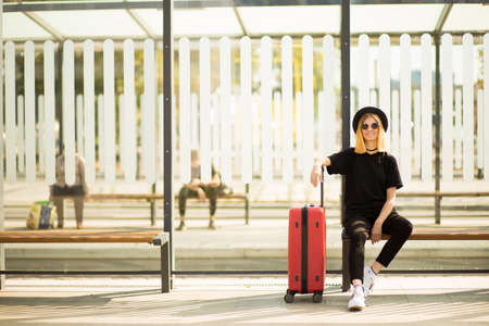 Full length portrait of stylish traveling young woman wear in total black with red suitcase wait for transport