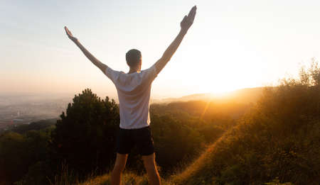 Silhouette of young man raises his hands up to sunset or sunrise on on top of hill in the summer