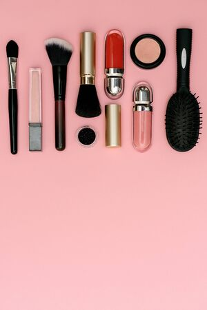glasses, lipstick, makeup brushes, flower lie on a pink background