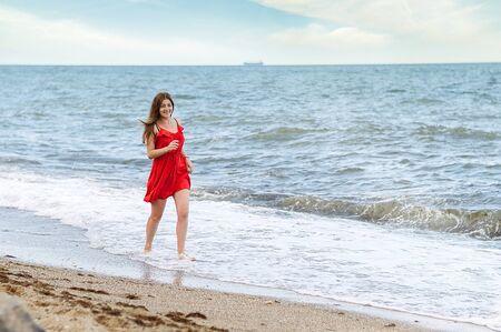 girl in a red dress by the sea walks along the sandy beach Standard-Bild