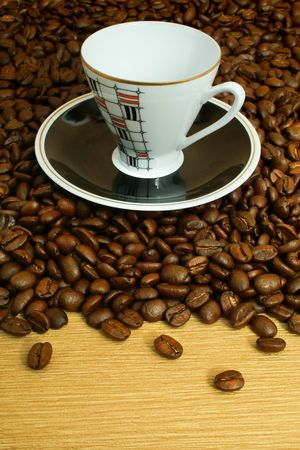 empty cup with saucer on coffee beans background photo