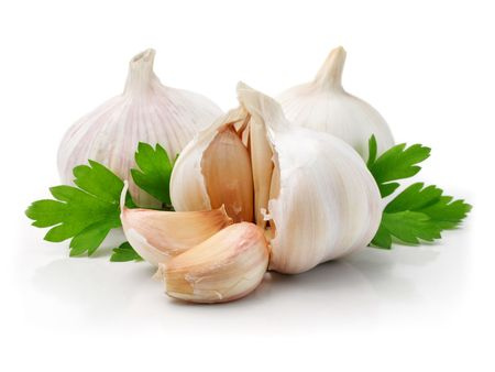 garlic: ripe garlic fruits with green parsley leaves isolated on white background Stock Photo