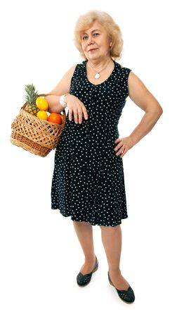 happy elderly woman with basket of fruits isolated on white background photo