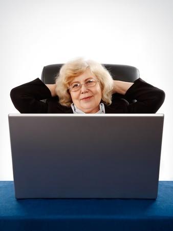 elderly businesswoman sitting in armchair by the laptop photo
