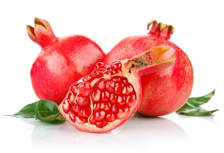 pomegranate fresh fruits with cut and green leaves isolated on white background Standard-Bild