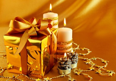 christmas gift in gold box with bow and candle