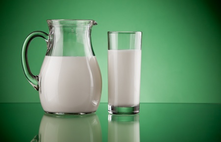 jugs: jug and glass with milk on green background