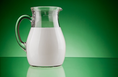glass jug  with milk on green background photo
