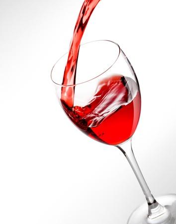 rode wijn, gieten in glas op grijze achtergrond