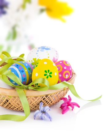 easter decorations: easter eggs in basket with bow isolated on white background