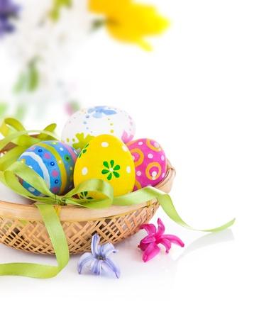 ornamentations: uova di Pasqua nel cestino con fiocco isolato su sfondo bianco Archivio Fotografico