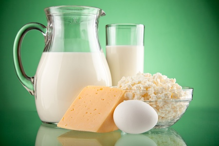 cottage cheese: jug and glass with milk on green background