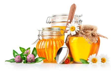 sweet honey in glass jars with spoon and flowers isolated on white background Stockfoto