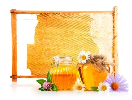 zoete honing in glazen potten en honingraat met bloemen geïsoleerd op een witte achtergrond Stockfoto