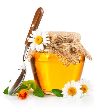zoete honing in glazen potten met lepel en bloemen geïsoleerd op witte achtergrond Stockfoto