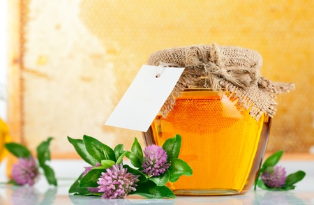 sweet honey in glass jars with flowers isolated on white background