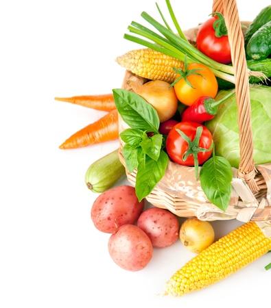 verse groenten met groene bladeren in de mand op een witte achtergrond Stockfoto