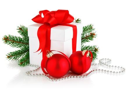 kerst cadeau met rode ballen boog en tak firtree geïsoleerd op witte achtergrond Stockfoto