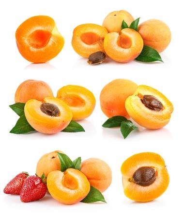set abrikoos vruchten met groen blad en worden verzaagd op een witte achtergrond Stockfoto