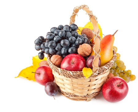 autumnal fruit in basket isolated on white background
