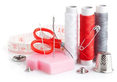 kit de costura: herramientas, tijeras, hilo de costura y una cinta métrica aisladas sobre fondo blanco
