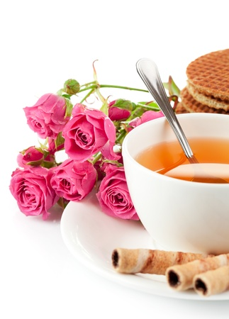 sweetmeats: tea in cup with biscuit and bouquet  roses isolated on white background