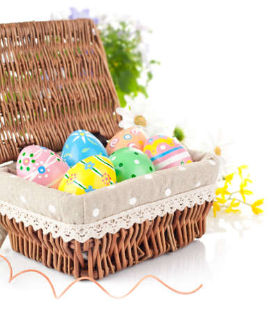 easter egg in basket with spring flower isolated on white background photo