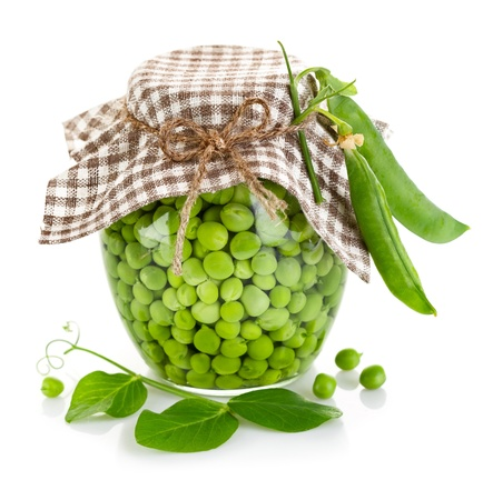 green peas in glass jar isolated on white background photo