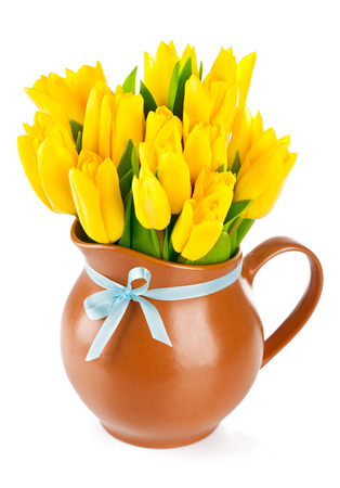 yellow tulips flowers in jug isolated on white background photo