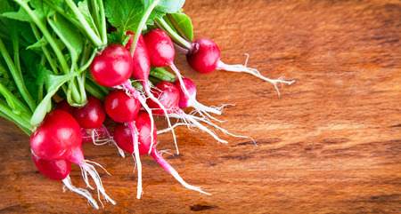 fascicle: bunch of radish with green leaves on wooden board Stock Photo