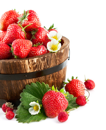 Fresh strawberry in wooden bucket with green leaf and flower. Isolated on white background photo