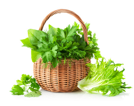 green herbs in braided basket isolated on white background photo