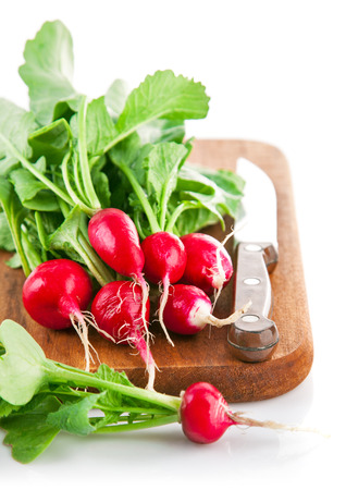 fascicle: Bundle radish on wooden board with knife. Isolated on white background