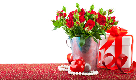unexpectedness: Bunch red roses with gift and heart. Isolated on white background