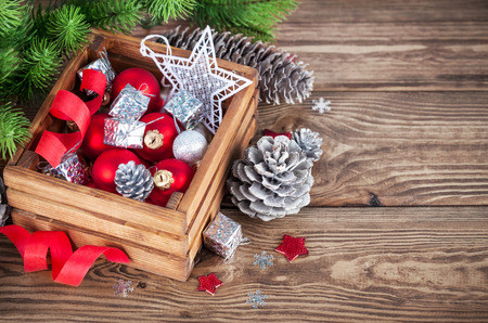 christmas ornamentation: Christmas red balls and ribbons in wooden box