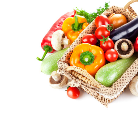 Fresh vegetables in wicker basket. Isolated on white background photo