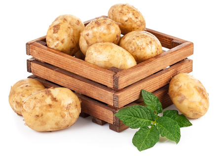 tare: New potatoes in box with green leaves. Isolated on white background Stock Photo
