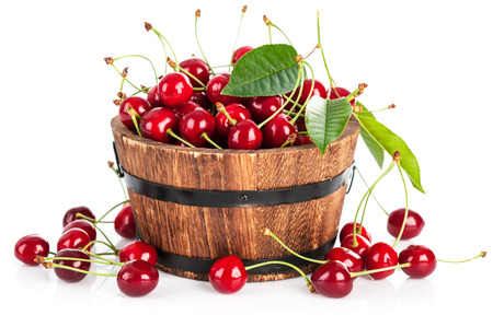 strewed: fresh cherry berries with green leaf isolated on white background