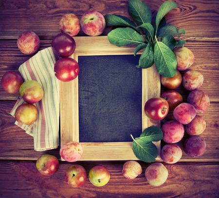 marco madera: Junta para el texto con ciruelas frescas y hojas verdes Foto de archivo
