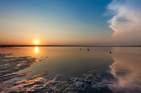 summer nature: sunset over water surface of salted sea bay