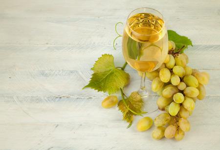 amoniaco: vino blanco de vidrio con uvas y hojas sobre tabla de madera