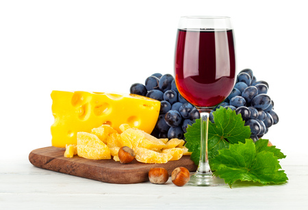 queso blanco: Vino tinto de vidrio con uvas y queso. Aislado en el fondo blanco