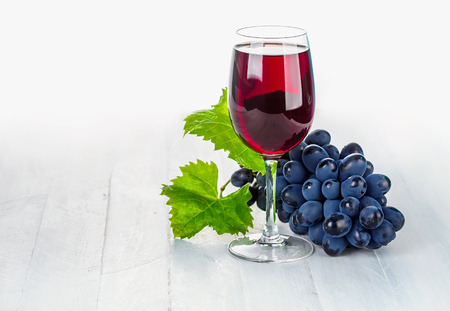 spirituous beverages: Glass red wine with cluster grapes