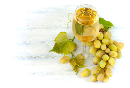 spirituous beverages: Glass white wine with grapes and leaf on wooden board Stock Photo