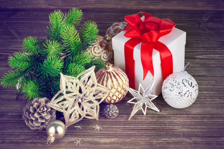 unexpectedness: Christmas still life with fir gift and tinsel on wooden board Stock Photo